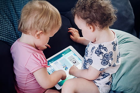 Two children interact with a tablet by tapping on the screen.